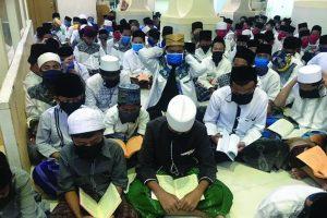 TETAP NGAJI: Santri Pondok Pesantren Baitul Burhan mengikuti pengajian menggunakan masker